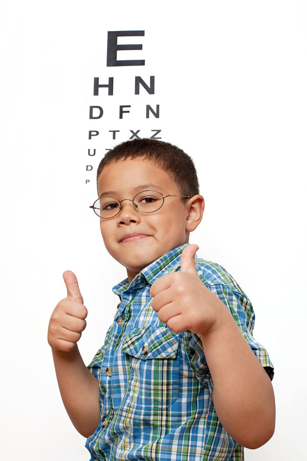 Cute little boywith glasses smiling and giving thumbs up sign, in front of eye chart in the background. Children at the eye doctor optometrist theme.